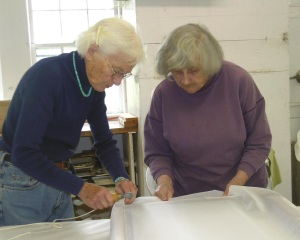 Nancy Freeman and Frances Hodsdon stretch new material onto silkscreen frames
