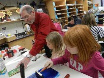 Dick Miller helps students print Christmas cards